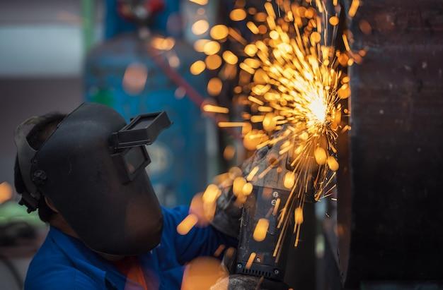 Het elektrische wiel malen op staalstructuur in fabriek