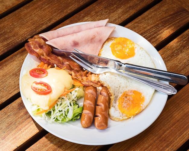 Het engelse ontbijt bestaat uit gebakken eieren, spek, worst en groene salade.
