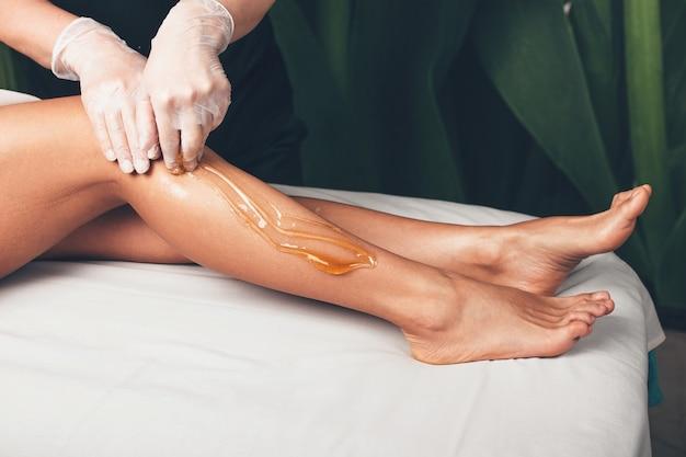 Het epileren van het haar van de benen gebeurt in een moderne wellness-salon door een vrouw die handschoenen draagt