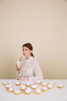 Het ernstige jonge dame stellen dichtbij cupcakes die koffie houden