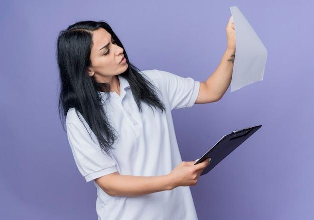 Het ernstige jonge donkerbruine kaukasische meisje houdt klembord en bekijkt document blad dat op purpere muur wordt geïsoleerd