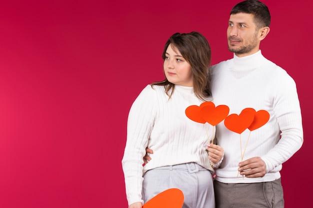 Het ernstige paar met grote kartonnen rode harten kijkt weg. rode achtergrond.
