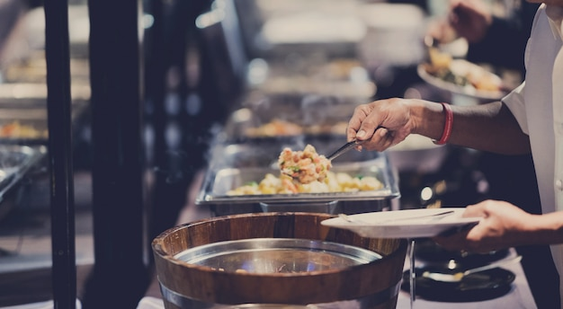 Het eten opscheppen, buffet eten in het restaurant, catering