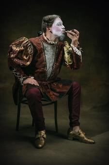 Het eten van een oester jonge man als johann bach geïsoleerd op donkergroene achtergrond