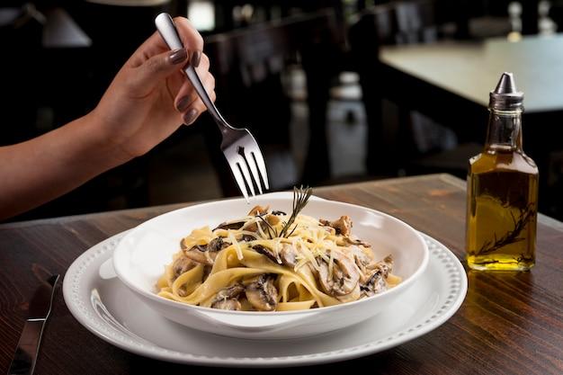 Het eten van luxe romige champignon fettuccine, in een restaurant - de hand van een jonge vrouw