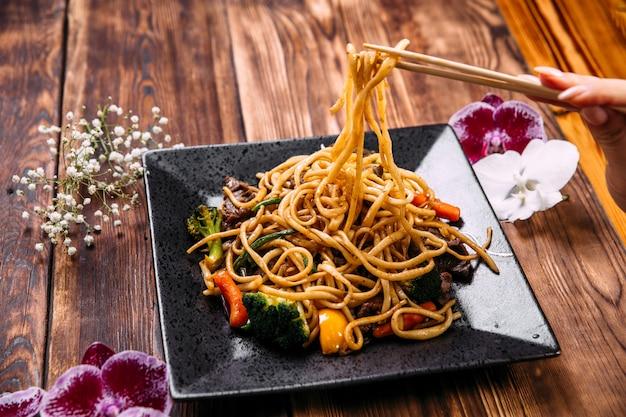 Het eten van rundvlees en groenten wok udon noedels