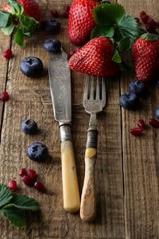 Het eten van verse aardbeien, vintage cuttleryvork en mes. geweven, rustieke houten lijst.