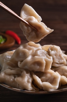 Het eten van verse, heerlijke gekookte dumplings, jiaozi op houten tafel achtergrond met sojasaus