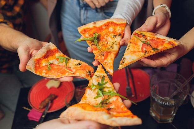 Het eten van voedselclose-up van mensenhanden die plakjes pepperonispizza nemen