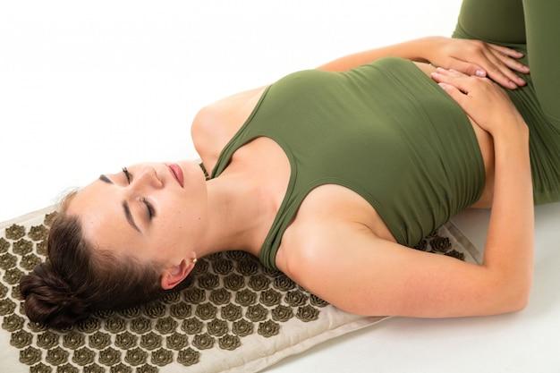 Het europese donkerbruine meisje in een groen sportenkostuum mediteert liggend op massagemat op wit