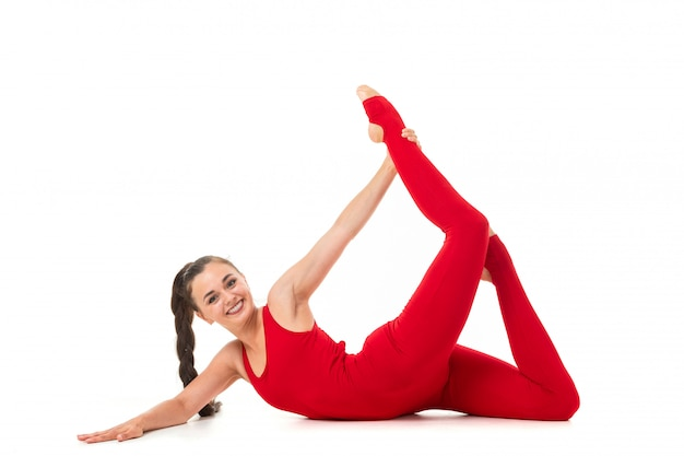 Het europese donkerbruine meisje in een rood sportenkostuum voert gymnastiek- oefeningen uit voor flexibiliteit geïsoleerde witte achtergrond