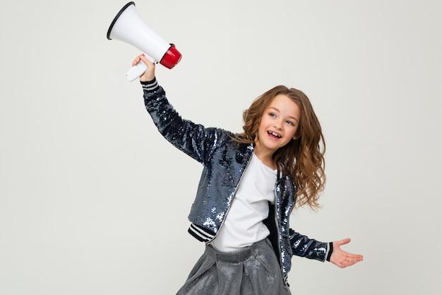 Het europese leuke glimlachende meisje met een megafoon meldt het nieuws met een megafoon in handen op een witte studiomuur