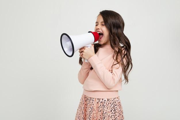 Het europese leuke glimlachende meisje met een megafoon meldt het nieuws met een megafoon in handen op een witte studiomuur Premium Foto