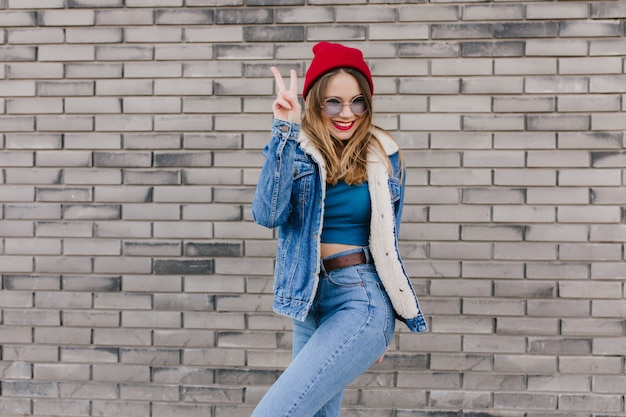 Het extatische blondemeisje in rode hoed die zich in vertrouwen bevinden stelt naast bakstenen muur. buiten schot van schattige blanke vrouw in spijkerbroek en denim jasje met plezier op straat.