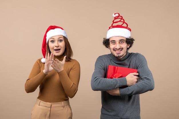Het feestelijke concept van de nieuwjaarsstemming met grappig gelukkig mooi paar dat rode hoeden van de kerstman op grijs draagt