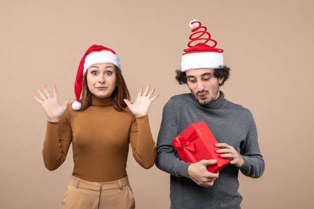 Het feestelijke concept van de nieuwjaarsstemming met grappig gelukkig mooi paar dat rode hoeden van de kerstman op grijs voorraadbeeld draagt