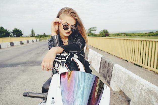 Het fietsermeisje in leer kleedt zich op een motorfiets