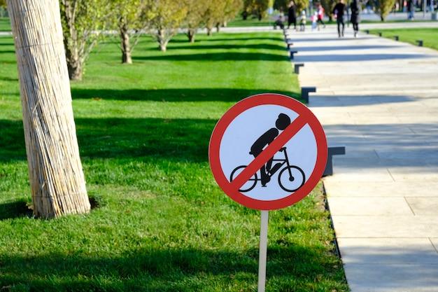 Het fietsverbodsbord op de houten paal bij de ingang van het park.