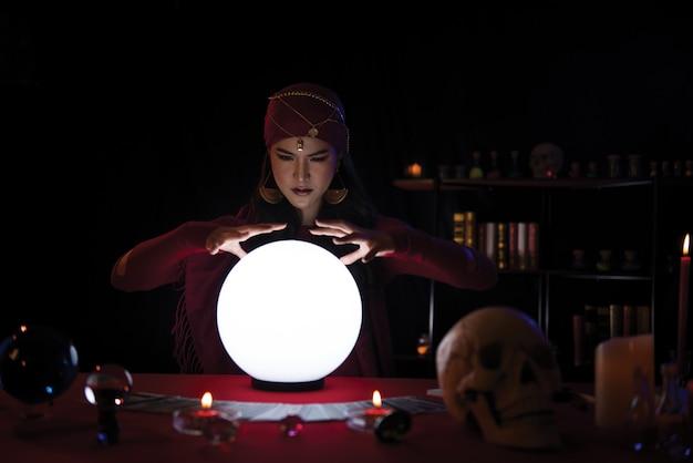 Het fortuinteller die van de vrouw met kristallen bol met decoratie werkt. portret vrouw waarzegster.