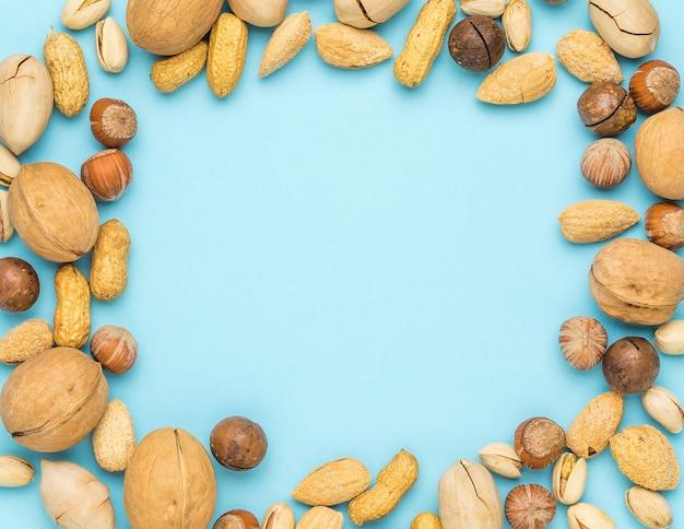 Het frame is gemaakt van een mengsel van een groot aantal noten op een blauwe achtergrond. vegetarisch eten.