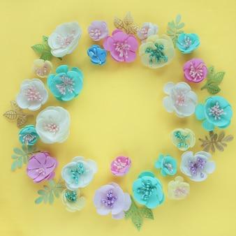 Het frame is gemaakt van kunstbloemen van roze wit blauw en geel op een lichtgele achtergrond van papier.