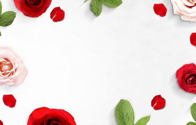 Het frame van rode en roze rozen en rozenblaadjes op de vloer