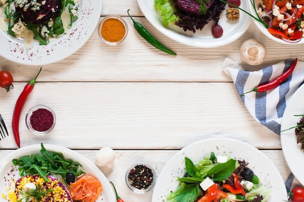 Het frame van verse groentesalades plat lag. bovenaanzicht op witte houten tafel met vrije ruimte voor tekst