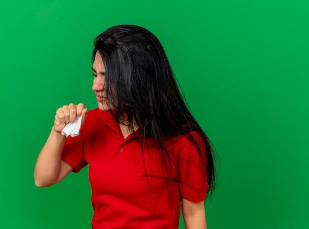 Het fronsende jonge zieke servet van de vrouwenholding hand in lucht met gesloten ogen houden die op groene muur wordt geïsoleerd