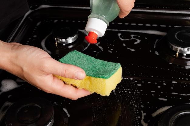 Het gasfornuis schoonmaken met een sopje. het schoonmaken van de keuken.