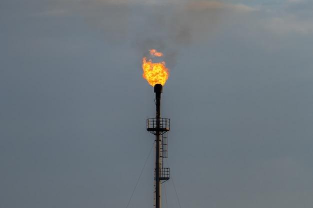 Het gastoorts van het raffinaderijbrand tegen de grijze hemel