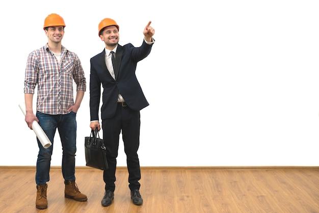 Het gebaar van de twee ingenieurs op de witte muurachtergrond