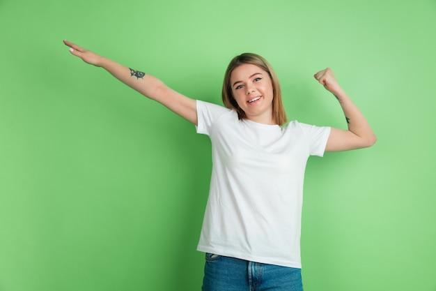 Het gebaar van de winnaar. het portret van de blanke jonge vrouw op de groene studiomuur