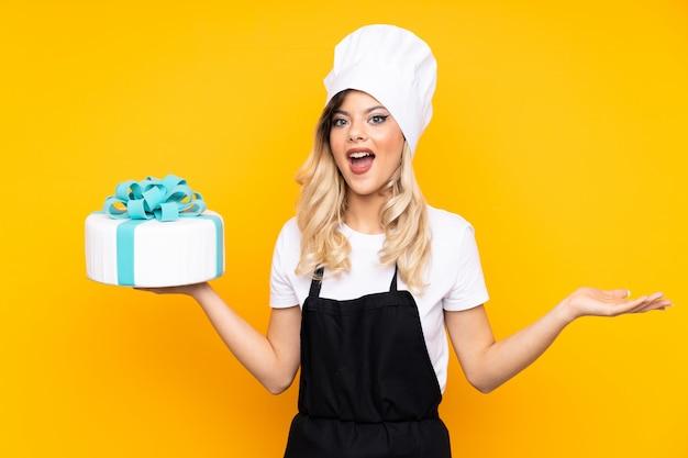 Het gebakje dat van het tienermeisje een grote cake op gele muur houdt die twijfels met verwarde gezichtsuitdrukking heeft