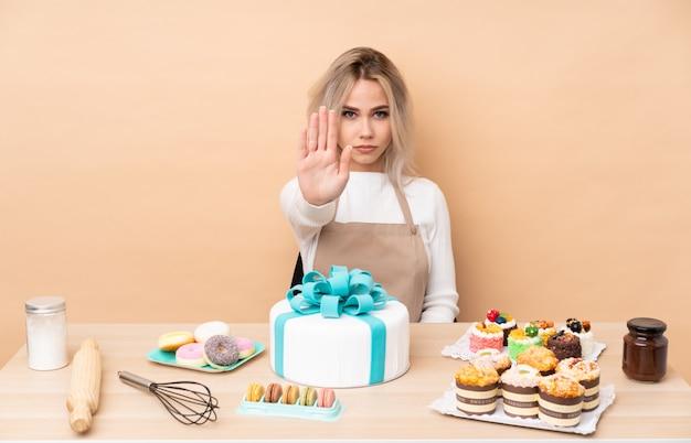 Het gebakjechef-kok van de tiener met een grote cake in een lijst die eindegebaar met haar hand maakt
