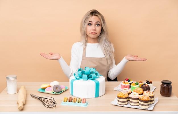 Het gebakjechef-kok van de tiener met een grote cake in een lijst die twijfels met verwarde gezichtsuitdrukking heeft