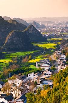 Het gebied en de dorpen van het raapzaadbloem bij het nationale geologische park van wanfenglin (bos van tien duizendenpieken), china
