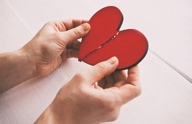 Het gebroken rode houten hart in de handen van de vrouw
