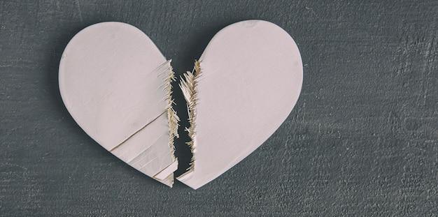 Het gebroken witte houten hart op de houten tafel. concept van de scheiding, verbroken relatie en het einde van de liefde