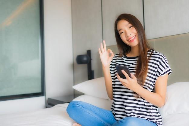 Het gebruik slimme mobiele telefoon van de portret mooie jonge aziatische vrouw in slaapkamer