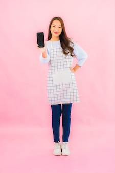 Het gebruik slimme mobiele telefoon van de portret mooie jonge aziatische vrouw op roze geïsoleerde muur