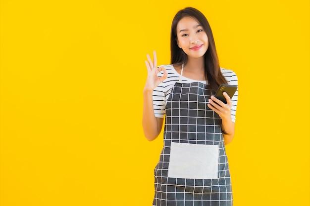 Het gebruik slimme mobiele telefoon van de portret mooie jonge aziatische vrouw