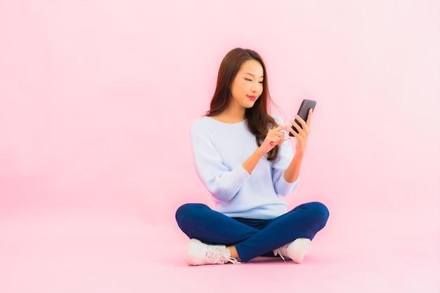 Het gebruik van de portret mooie jonge aziatische vrouw slimme mobiele telefoon op roze kleur geïsoleerde muur