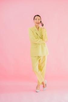 Het gebruik van portret mooie jonge aziatische bedrijfsvrouw slimme mobiele telefoon met koffiekop op kleur