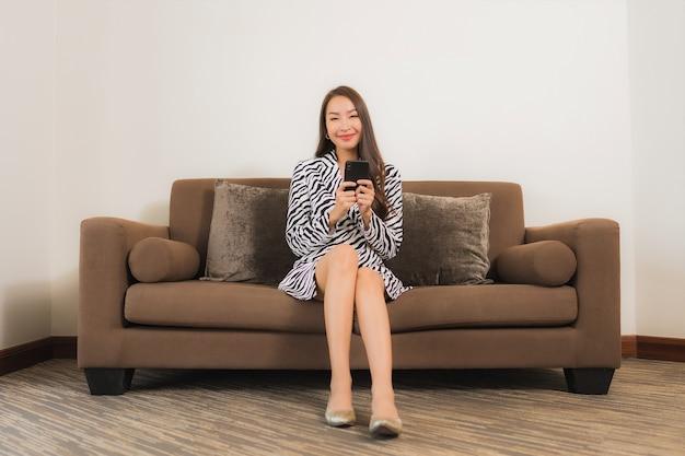 Het gebruik van slimme mobiele telefoon van de portret mooie jonge aziatische vrouw op bank in woonkamerbinnenland
