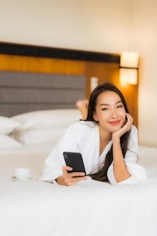 Het gebruik van slimme mobiele telefoon van de portret mooie jonge aziatische vrouw op bed in slaapkamerbinnenland