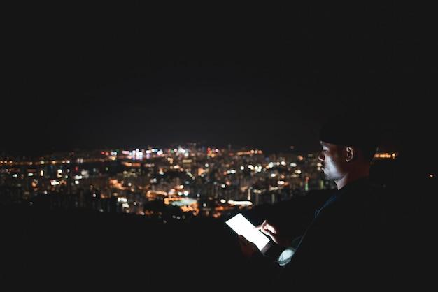 Het gebruiken van tablet over het uitzicht van de bergstad bij nacht