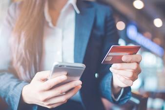 Het gebruikscreditcards en smartphones van de bedrijfsvrouwenhand.