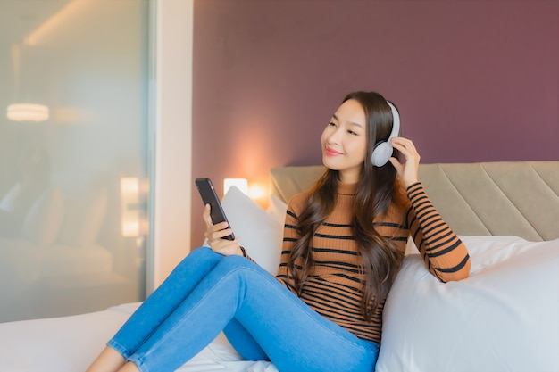 Het gebruikshoofdtelefoon van de portret mooie jonge aziatische vrouw om muziek op bed te luisteren