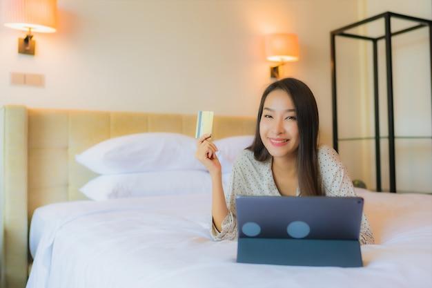 Het gebruikstablet van de portret mooie jonge aziatische vrouw met creditcard op bed