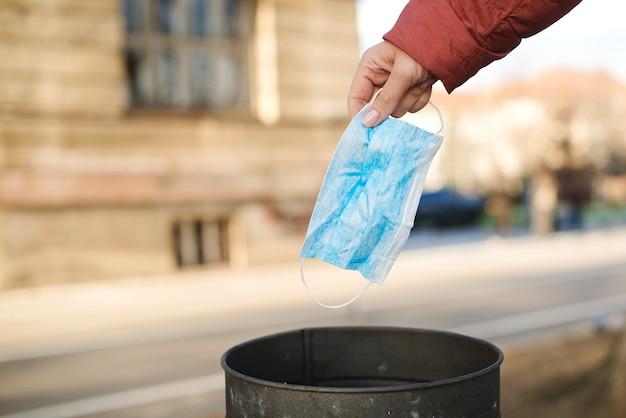 Het gebruikte gezichtsmasker wordt in een prullenbak gedumpt. wereld coronavirus-uitbraak. wereldwijde pandemie. coronavirus-quarantaine.